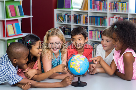 children with globe on table