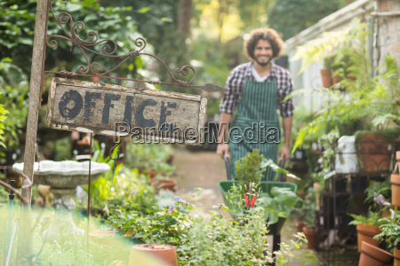 office placard by plants while gardener