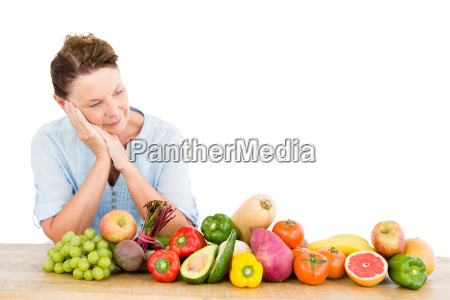 thoughtful woman standing by fruits and