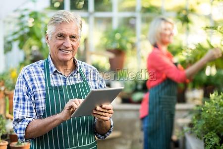 senior man using digital tablet while