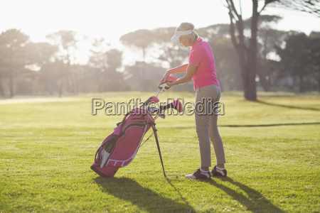 side view of woman putting golf