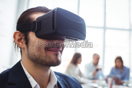 smiling businessman using virtual reality simulator