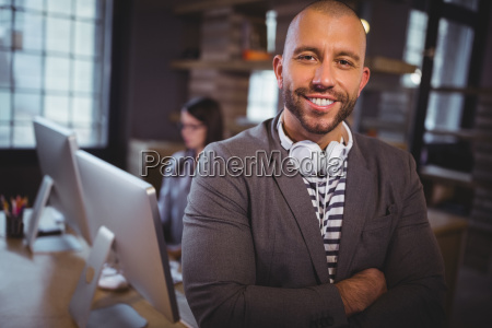 confident creative businessman standing by desk