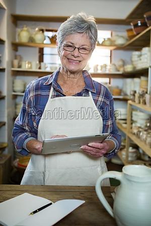 happy female potter using digital tablet