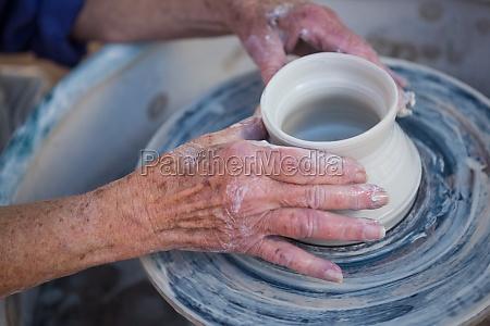 close up of potter making pot