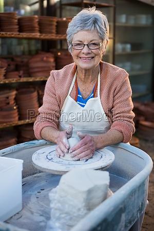 female potter making pot