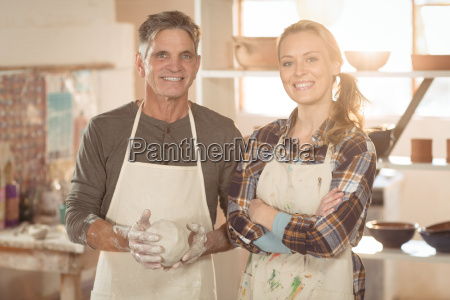 smiling potters standing in pottery shop