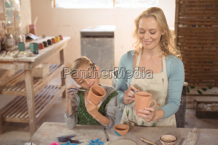 female potter and girl painting in