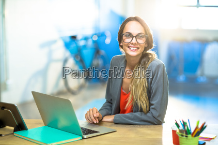 woman sitting on desk and using