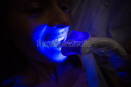 dentist examining a female patient with