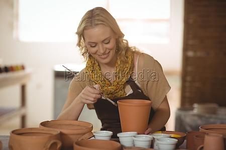 beautiful female potter painting on pot