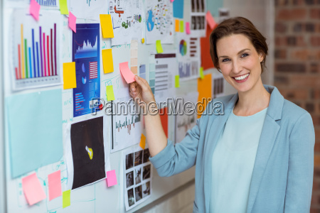 businesswoman putting sticky notes on whiteboard