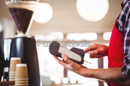 mid section of waiter using credit