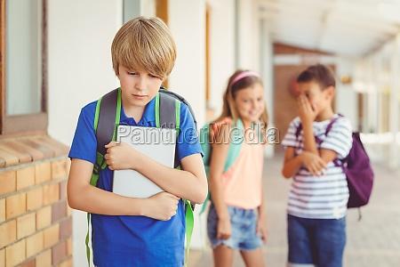 school friends bullying a sad boy