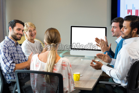 coworkers applauding a colleague during a