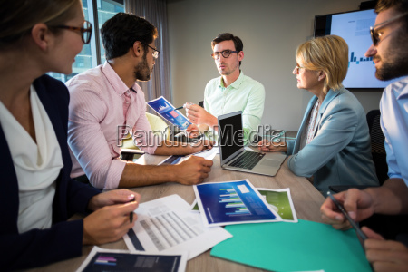 business people discussing over graph during