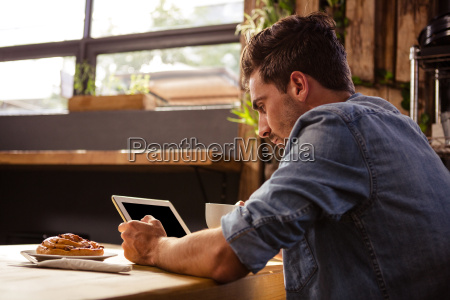 man drinking coffee and using tablet