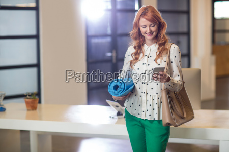 smiling woman using phone while holding