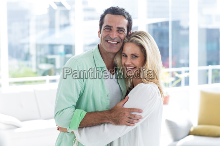 mid adult romantic couple hugging at