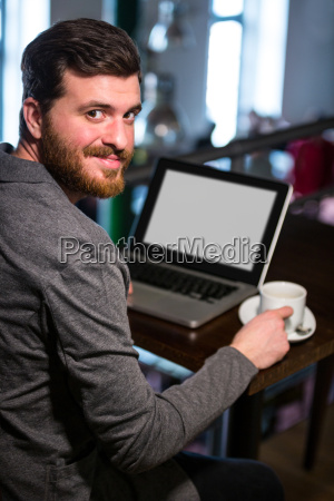 man holding coffee cup and using
