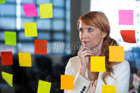 thoughtful businesswoman looking at sticky notes