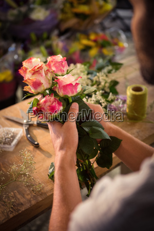 male florist preparing flower bouquet