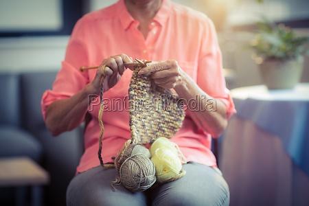 senior woman knitting wool