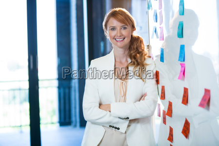 smiling businesswoman leaning on whiteboard
