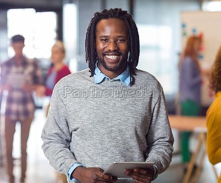 portrait of smiling man holding digital