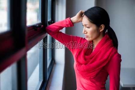 thoughtful young woman by window
