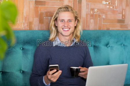smiling man using mobile phone while