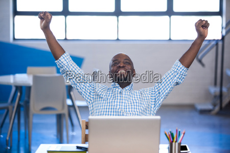 businessman raising his arms front of
