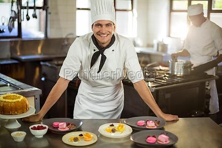 portrait of smiling chef presenting dessert