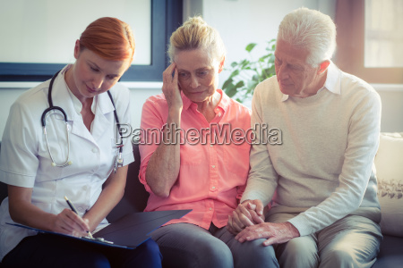 doctor writing medical report of senior