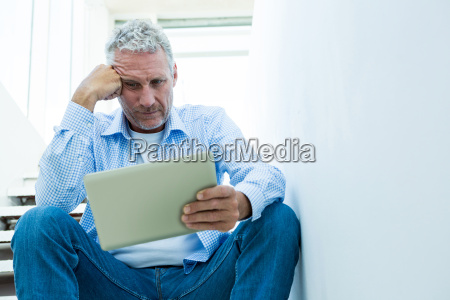 tensed mature man holding tablet while