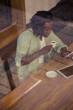 man drinking coffee and using smartphone