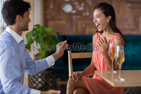 man proposing to woman offering engagement