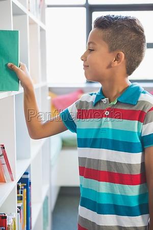 boy taking a book from bookshelf