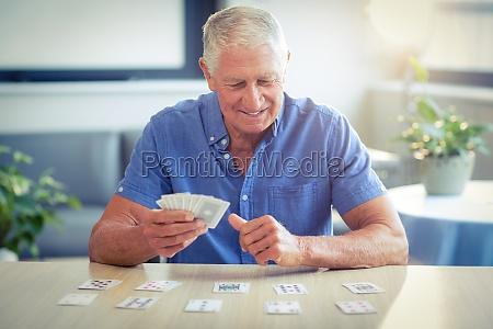 senior man playing cards in living