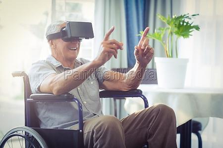happy senior man on wheelchair using