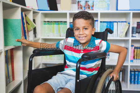 disabled boy selecting a book from