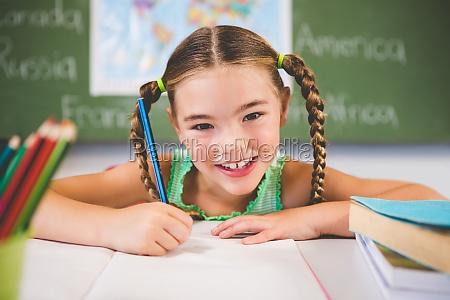 portrait of smiling schoolgirl doing homework