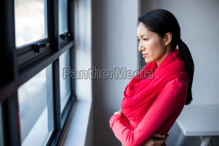 thoughtful woman standing by window in