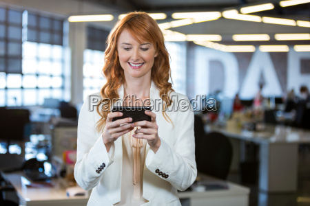 businesswoman using cellphone while standing