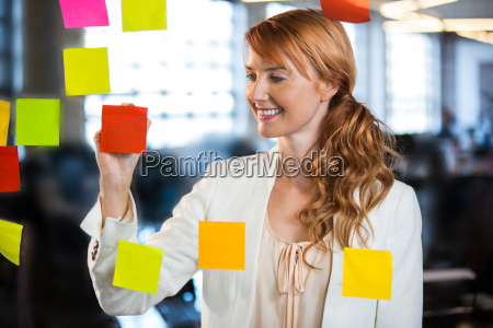 businesswoman writing on adhesive notes