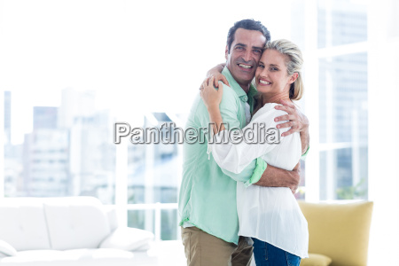 mid adult smiling couple hugging at