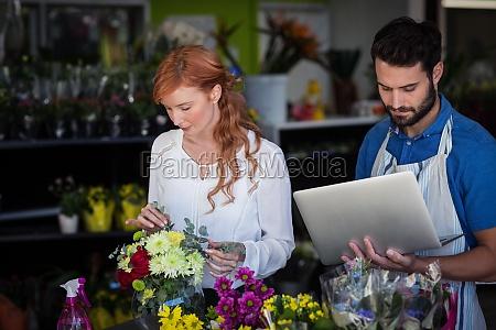 woman preparing flower bouquet while man