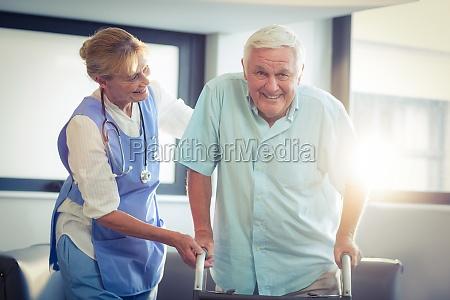 female doctor helping senior man to
