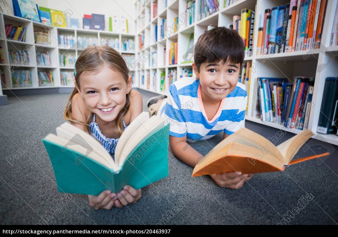 Stock Photo 20463937 - Happy school kids lying on floor and reading a book  in library