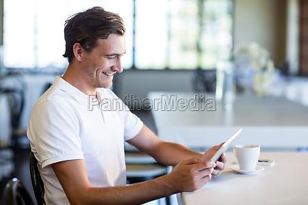 happy man using digital tablet